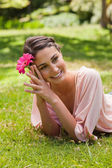 Woman lying on her front while holding a flower against her head — Stock Photo