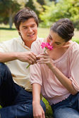Woman smelling a flower which is being given to her by a man — Stock Photo