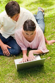 Two friends looking into a laptop together while lying down — Stock Photo