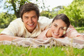 Two friends smiling and looking ahead while lying on a blanket — Stock Photo