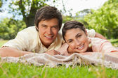 Two friends lying together on a blanket while smiling — Stock Photo