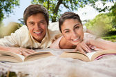 Two friends reading books while lying on a blanket — Stock Photo