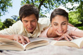 Two friends smiling while reading books as they lie down — Stock Photo