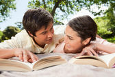 Two friends looking at each other while reading books on a blank — Stock Photo