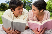 Two friends smiling at each other while reading on a blanket — Stock Photo