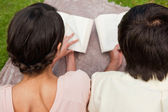 Rear view of two friends reading while on a blanket — Stock Photo