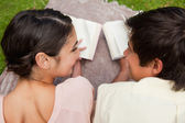 Rear view of two friends looking at each other while reading on — Stock Photo
