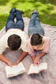 Elevated view of two friends reading while on a lying down — Stock Photo