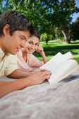 Woman looking to the side as she reads with her friend in a park — Stock Photo