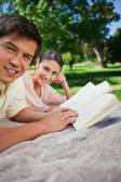Two friends looking to the side while reading in a park — Stock Photo