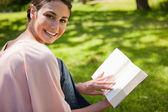 Femme regarde à côté d'elle tout en lisant un livre dans l'herbe — Photo