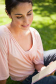Woman smiling while reading a book as she sits on grass — Stok fotoğraf