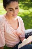 女人微笑时,她坐在草地上读一本书 — 图库照片