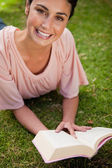 Smiling woman looking up while reading a book as she lies down — Stock Photo