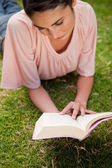 Woman looking down at a book while lying in grass — Stock Photo