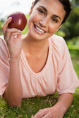 Woman holding an apple while lying in grass — Stock Photo