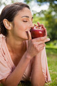 Woman smells an apple while lying in grass — Stock Photo