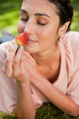 Woman smells an strawberry while lying in grass — Stock Photo
