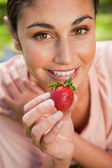 Woman offering a strawberry while lying in grass — Stock Photo