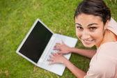 Woman looking to her side while using a laptop — Stock Photo