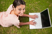 Woman looking upwards while using laptop — Stock Photo