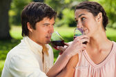 Two friends drinking wine while linking arms — Stock Photo