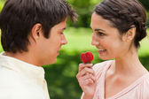 Woman looking at her friend while holding a strawberry — Stock Photo