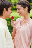 Woman laughing while offering a strawberry to her friend — Stock Photo