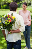 Man about to surprise his friend with a bouquet of flowers — Stock Photo