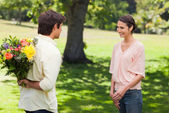 Woman smiling as her friend approaches her with flowers — Stock Photo