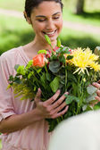Woman looking at flowers which have been given to her — Stock Photo