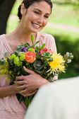 Woman holding flowers which she has been given — Stock Photo