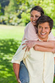 Woman holding her friend tight as he is carrying her on his back — Stock Photo