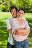 Man smiling as his he holds onto his friends waist — Stock Photo