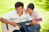 Woman leaning while leaning on her friends shoulder as he plays — Stock Photo