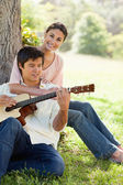 Woman holding her friend as her plays the guitar — Stock Photo