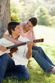 Woman looking at her friend while holding him as her plays the g — Stock Photo