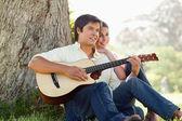Mężczyzna gra na gitarze patrząc do odległości z jego — Zdjęcie stockowe