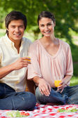 Woman and her friend smiling while holding glasses of juice duri — Stock Photo