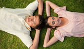 Two friends lying head to head with both hands behind their neck — Stock Photo