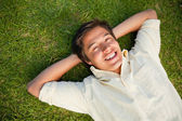 Man smiling as he lies with both hands behind his neck — Stock Photo