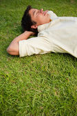 Man lying in grass with his eyes closed and both hands behind hi — Stock Photo