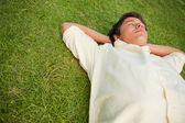 Man lying in grass with his eyes closed and his head resting on — Foto de Stock