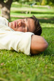 Man lying with his eyes closed and the side of his head resting — Foto Stock