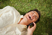 Man laughing while making a call while using a phone as he lies — Stock Photo