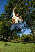 Man looking down to the ground as he jumps with his arms raised — Stock Photo