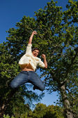 Man raising his arms and legs as he jumps in celebration — Stock Photo