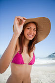 Young smiling woman holding her hat brim while wearing a pink sw — Stock Photo