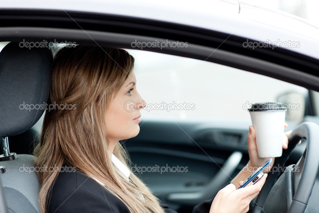 Blond businesswoman sending a text while driving to work — Stock Photo #10320481