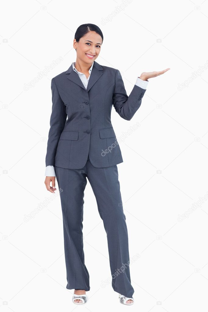 Smiling businesswoman presenting with her palm up against a white background — Stock Photo #10321863